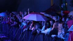 Rainy Concert A crowd of young people in front of the stage behind the fence Stock Footage