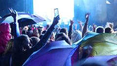 Rainy Concert People raise their hands at a concert in the rain with umbrella Stock Footage
