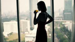 Young woman drinking cocktail and admire view from window Stock Footage