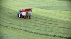 Tractor is picking up grass Stock Footage