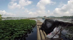 Bamboo raft floating on polluted lake - stock footage