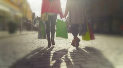 Low angle view two female friends walking with colourful shopping bags Stock Footage