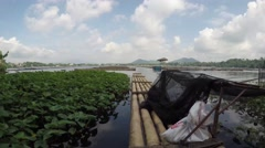 Bamboo raft floating on polluted lake Stock Footage