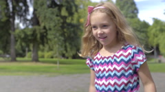 Stock Video Footage of Little Girl Walks In Park, Filled With Curiosity, Runs To Duck Pond (4K)