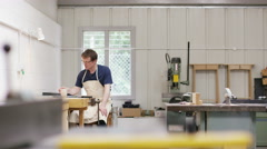 4K Furniture maker in his workshop, having a hot drink while he works on designs - stock footage