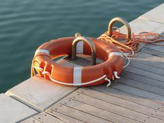 Orange life buoy on wooden pier in the harbor Stock Photos