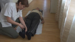 Senior white man at medical cabinet testing reflexes, young woman doctor nursing - stock footage