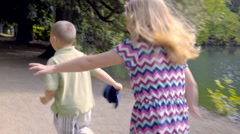 Little Girl Chases Her Brother Through Park, Catches Him, Tickles Him Stock Footage
