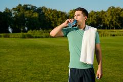 Beautiful sportsman drinking water on the lawn. - stock photo