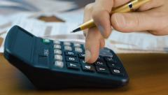 A man looks at utility bills and use the calculator - stock footage