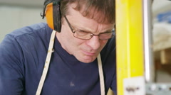 4K Professional carpenter in his workshop, cutting timber with a band saw Stock Footage