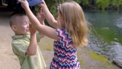 Kids Play With Hat, They Hide Behind It, Then Run, Sister Tickles Brother Stock Footage