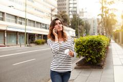 Horizontal portrait of a young lady looking away while walking outdoors and t Stock Photos