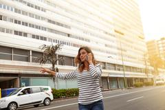 Young woman calling a taxi on city avenue while talking on mobile phone - stock photo