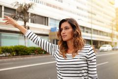 Stock Photo of Waist up portrait of a beautiful woman of caucasian ethnicity hailing a cab d