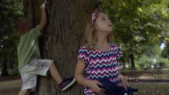 Cute Little Kids Climb Big Tree, Little Girl Holds Out Hat With Leaves In It Stock Footage