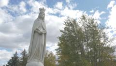 4K Statue Lady Of Peace Christian Monument Trees Clouds Sky Dunvegan  Hand Held Stock Footage