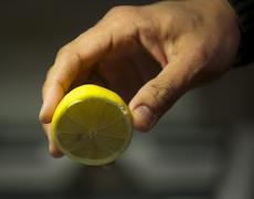 Man's hand squeezing lemon Stock Photos