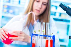 young female scientist works in laboratory wearing white coat - stock photo