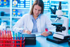 Young female scientist works in laboratory wearing white coat Stock Photos