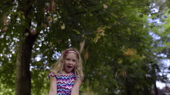 Happy Little Girl Throws Leaves In Air, She Brushes Leaves Out Of Her Hair Stock Footage