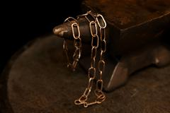 Handcrafted chain draped over an anvil Stock Photos