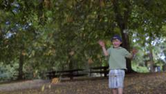 Adorable Little Boy Plays In Park, Throws Leaves In The Air, Runs Away (4K) Stock Footage