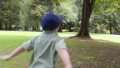 Little Boy Pretends To Fly, Spreads Arms Out, Runs Fast Through Park (4K) Stock Footage