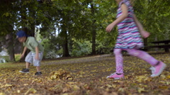 Little Kids Play In Park, Boy Gathers Leaves For Leaf Pile (4K) - stock footage
