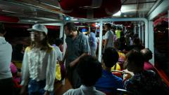 Express boat interior night time, passengers walk to exit at aisle, some sitting Stock Footage