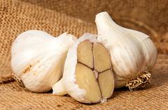 Two whole and half head of garlic - stock photo