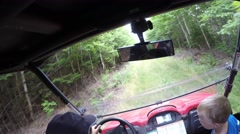 A high shot of family riding a side by side vehicle in thick green forest Stock Footage