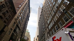 Driving upward angle view of Empire State Building with FedEx truck in NYC Stock Footage