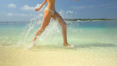 SLOW MOTION: Young woman running in surf at sandy beach Stock Footage