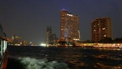 Luxury riverside hotel tower at night, parallax shot from moving boat Stock Footage