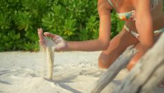 SLOW MOTION: Young woman playing with sand at exotic beach Stock Footage