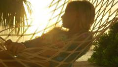 SLOW MOTION: Woman lying in hammock on exotic beach at sunset Stock Footage