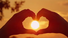 CLOSE UP: Making heart with hands over the setting sun Stock Footage