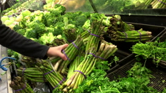Woman selecting asparagus in grocery store - stock footage