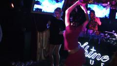 Two girls on club stage. Black and red dress. Sexual dancing Stock Footage