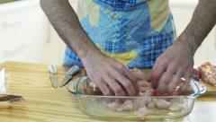 Man adding seasonings on chicken meat in kitchen at home Stock Footage