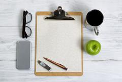 Clipboard with office supplies and snack foods on a white wooden desktop - stock photo