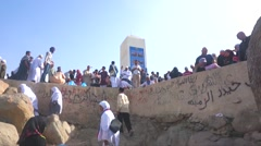 Pilgrims climb to top of Jabal Rahmah (Rahmah Hill) at Arafah, Mecca Stock Footage