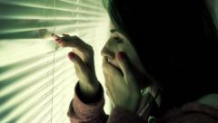 Scared woman looking out the window Stock Footage