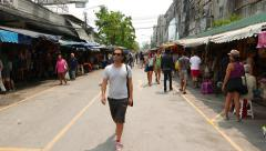 Tourist man in dark sunglasses walk along Chatuchak Weekend market, glide shot Stock Footage