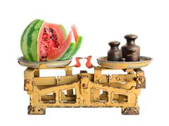 Sliced ripe watermelon on the old fashioned scales with kettlebells. Isolated - stock photo