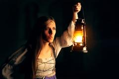 Curious Medieval Princess Holding Lantern Looking Outside - stock photo