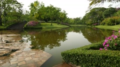 Queen Sirikit Park rock pathway across pond canal, pan shot, green garden Stock Footage