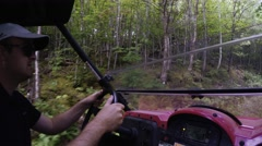 A wide shot of man steering a side by side vehicle in thick green forest Stock Footage