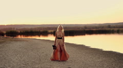 Young girl in a beautiful dress is on the shore  of the lake at sunset Stock Footage